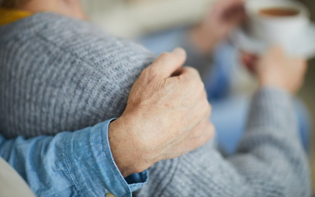 Image - hand resting on the shoulder of a person wearing a cardigan and holding a cup and saucer